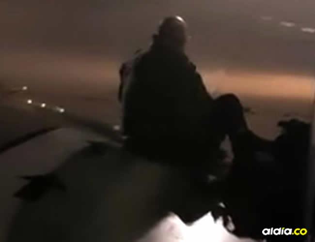En las imágenes publicadas en su cuenta de Facebook, se ve a un hombre que camina sobre el ala y se coloca su mochila en la espalda antes de sentarse | AFP