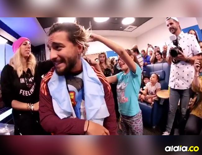 El cantante Maluma mientras una niña le cortaba el cabello con unas tijeras. | Instagram