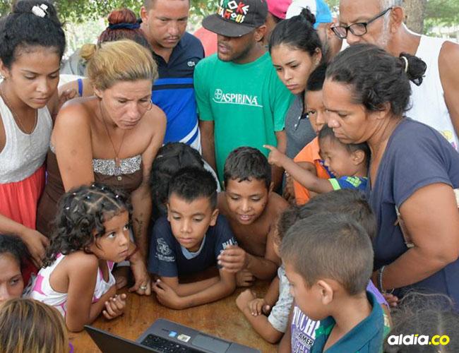 Un grupo de venezolanos mira en un computador la posesión de Nicolás Maduro.