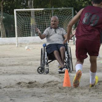 Omar Polo en plena faena desde la raya de cal dirigiendo en silla de ruedas a sus pupilos.