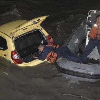 Tres miembros de la Armada, en una lancha, ayudan a recuperar el vehículo tras caer en el río Magdalena.
