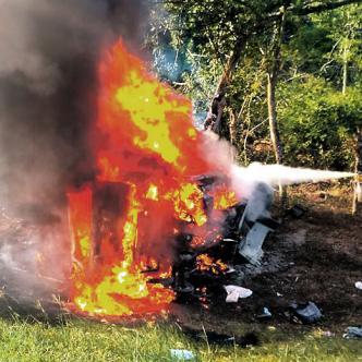 Un voluntario trata de apagar las llamas en la camioneta tipo van. | Foto: AL DÍA
